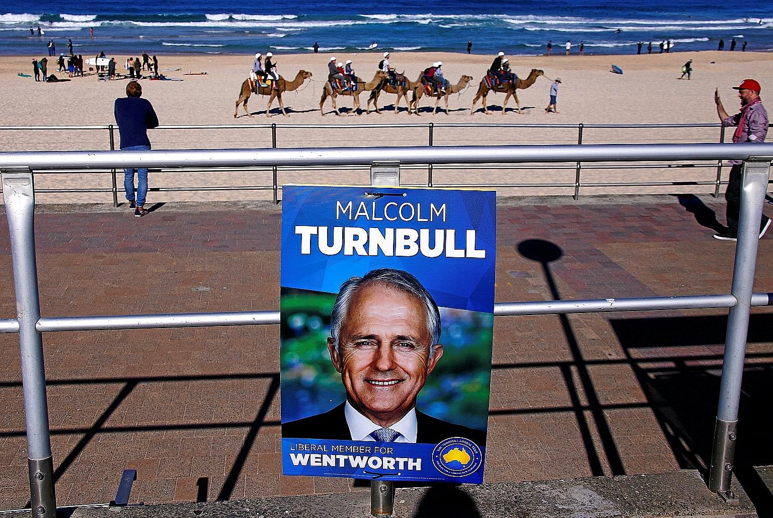 An election campaign poster of Australian Prime Minister Malcolm Turnbull against a backdrop of tourists riding camels along Bondi Beach in Sydney. Commentators have criticised Mr Turnbull's campaign, which appeared to lack energy and relied on a som