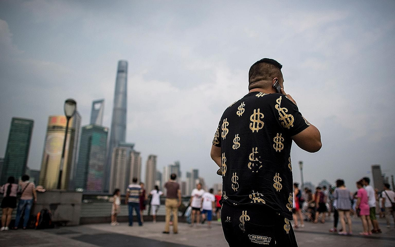 Dollars seem to be on this man's mind as he walks by Shanghai's financial district. As China's economy steadies and consumer spending increases, the prospects of many emerging markets are also improving.