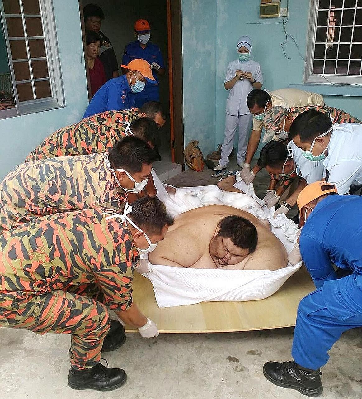 A thick cloth and a hardwood board were needed to help firemen and paramedics carry Mr Sia from his house in Sibu to a lorry to transport him to hospital.