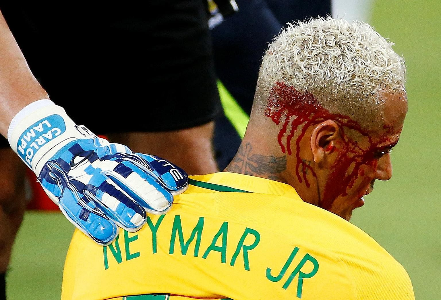 Brazil's Neymar is helped by Bolivia goalkeeper Carlos Lampe after Yasmani Duk leaves the forward with blood pouring from his head.