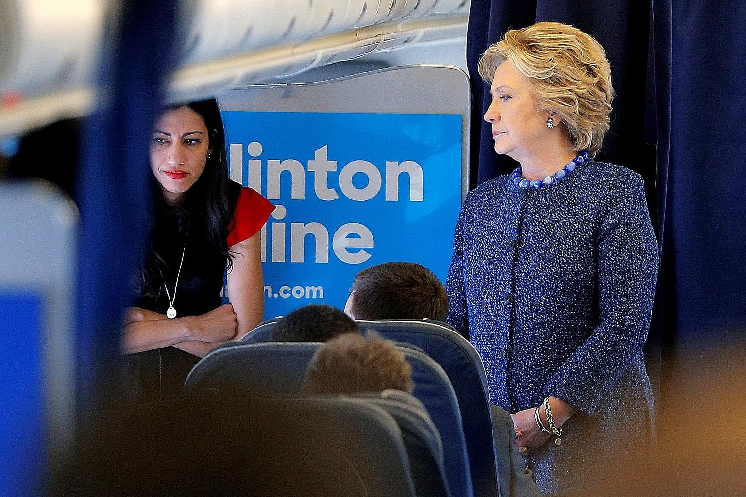 Mrs Clinton with her aide Huma Abedin onboard her campaign plane on Friday. The e-mail that triggered the current scandal surfaced because of investigations into sexual messages allegedly sent to a minor by Ms Abedin's husband, former congressman Ant
