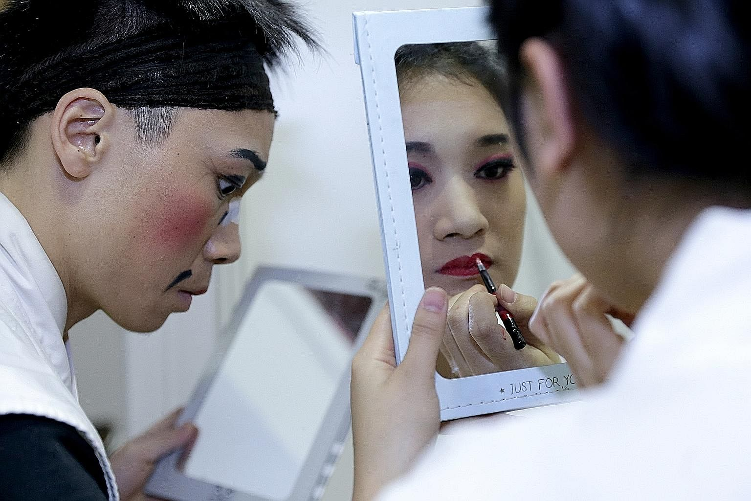 Members of the Xiao Mei Hua Opera Troupe preparing back