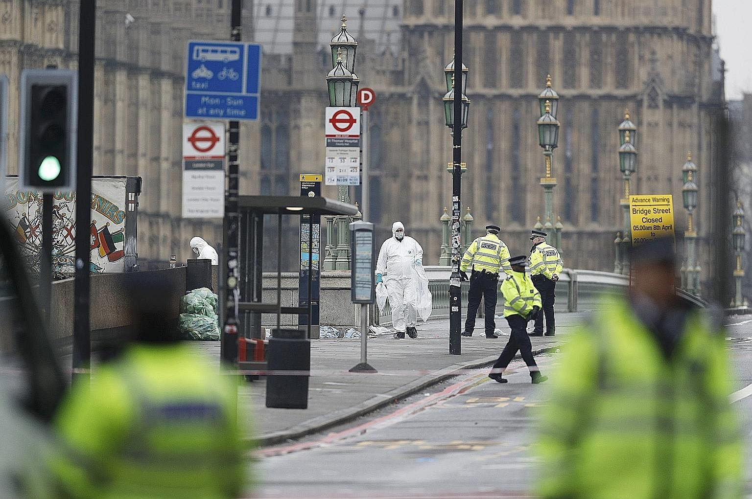 Police officers and forensics investigators working on Westminster Bridge yesterday after an attack by a man driving a car and wielding a knife left four people dead. A police officer entering a building in Birmingham, one of the properties raided af
