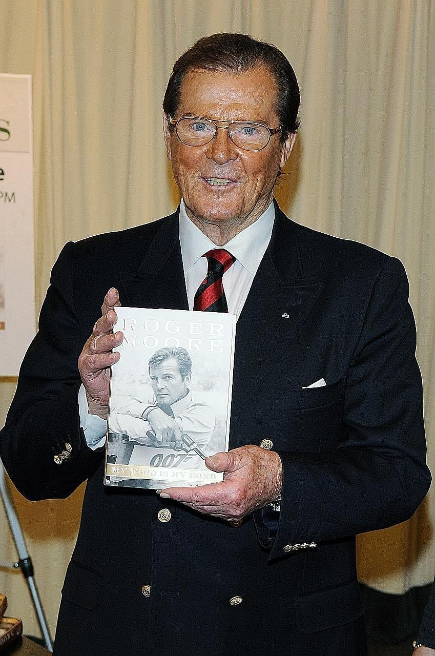 Roger Moore with his memoir My Word Is My Bond in 2008 in New York City.