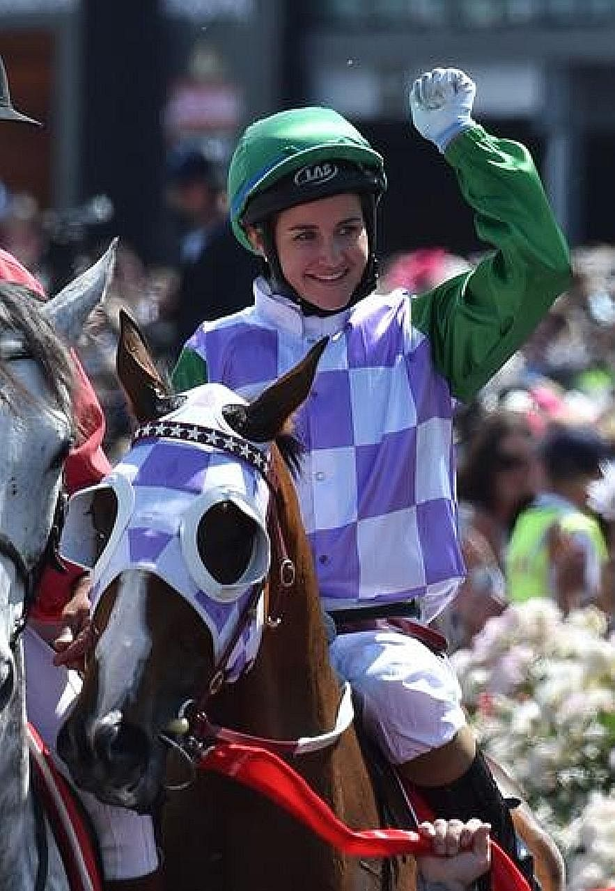 Jockey Michelle Payne punching the air after becoming the first female jockey to win the 155-year-old Melbourne Cup in 2015.