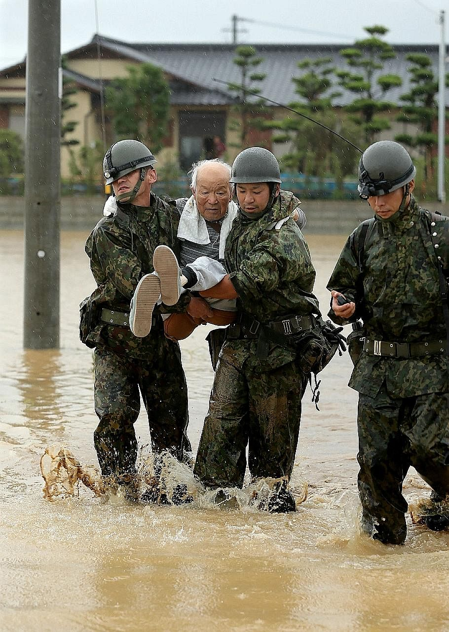 These soldiers rescuing an elderly man in Asakura were among thousands of police officers and tro