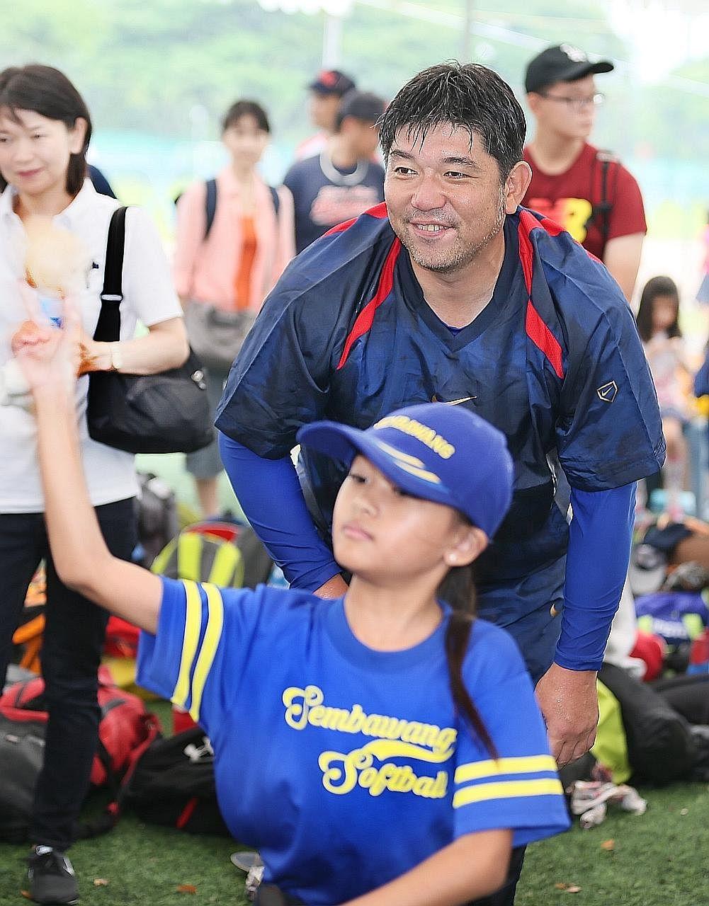 Retired Japanese baseball great Hideo Nomo observing Sembawang Primary School pupil Shirfa Syafiyah's pitching technique at the Kallang Softball Diamond yesterday.