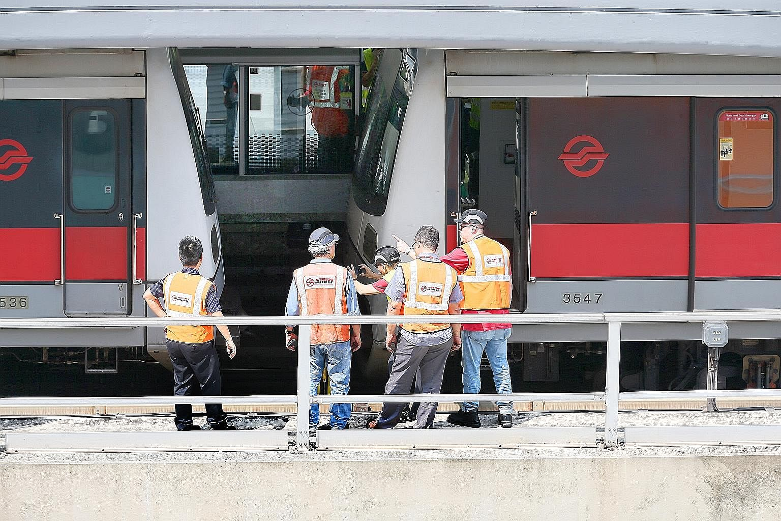 SMRT officials examining the two trains on the East-West Line which collided at Joo Koon MRT station last month, injuring 38 people.