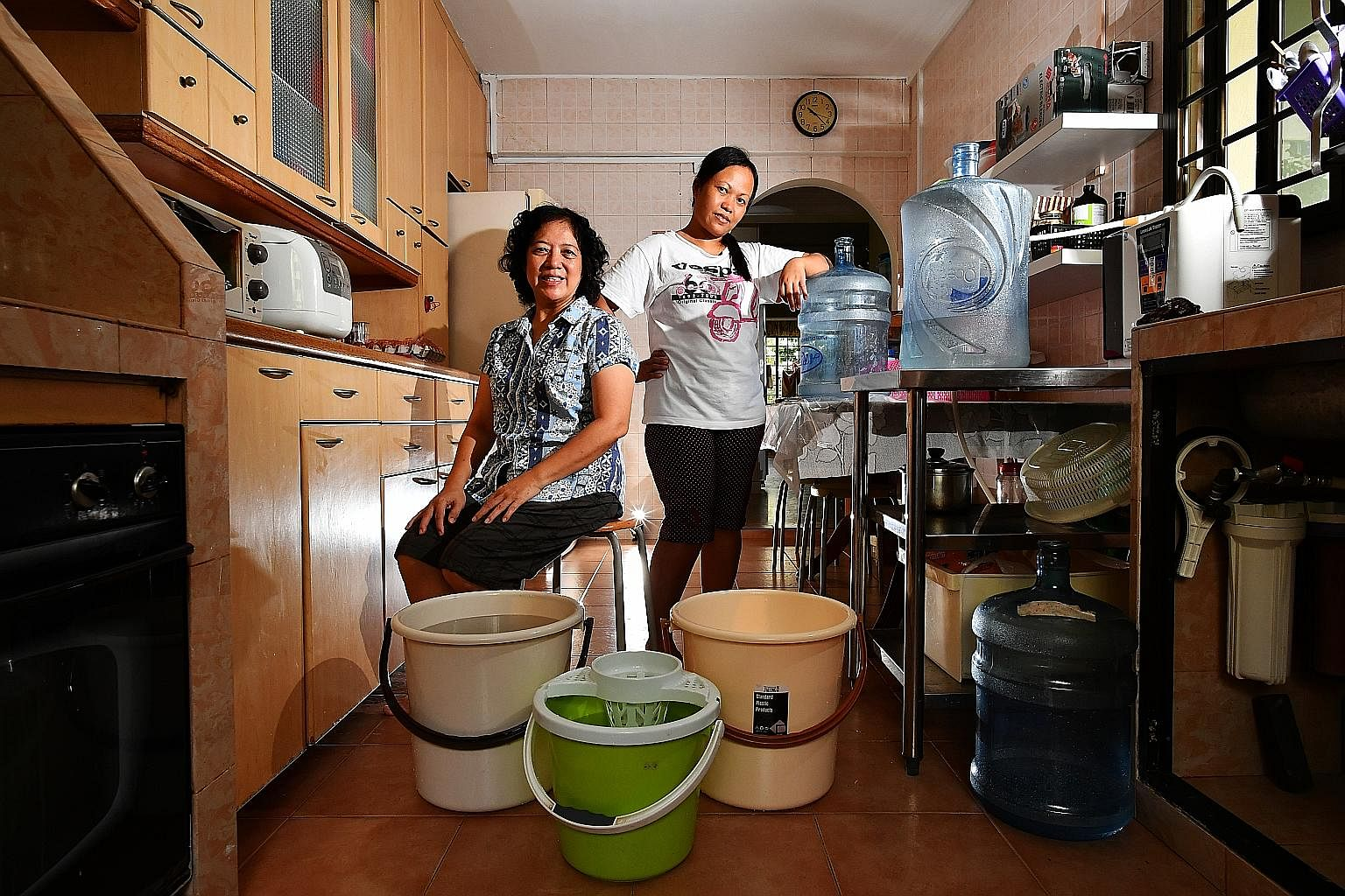 Madam Yeong Soh Yeng, a freelance pre-school teacher, and her Indonesian maid, Madam Fatimah Dulhadi, save water from the washing machine's rinse cycles to wash the floors and flush toilets.