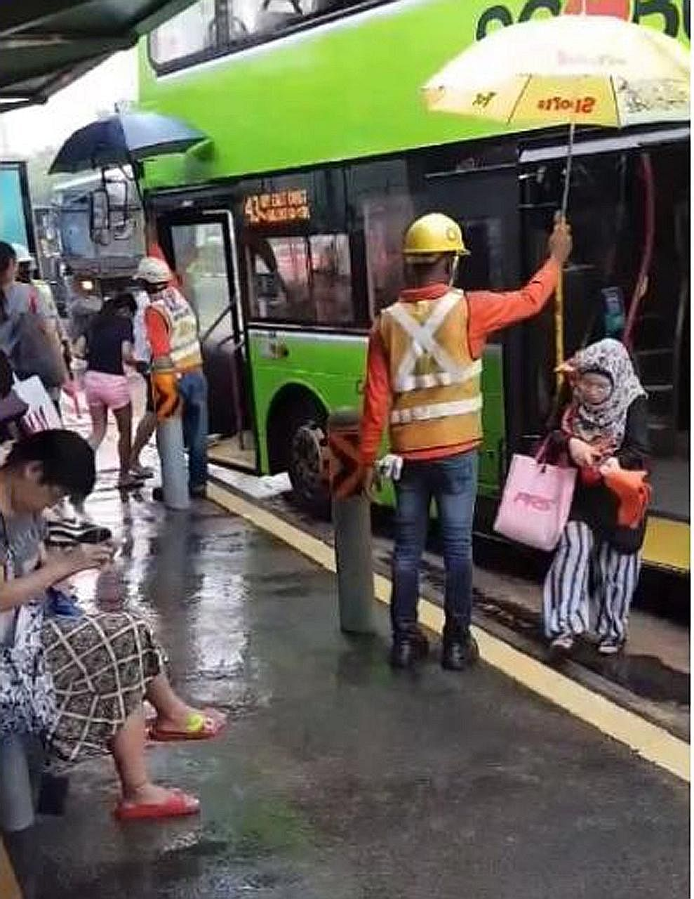 The foreign workers, armed with an umbrella each, stationed themselves at a bus stop in Sengkang at around 10am on Monday to shelter commuters boarding and alighting from buses in the heavy rain.