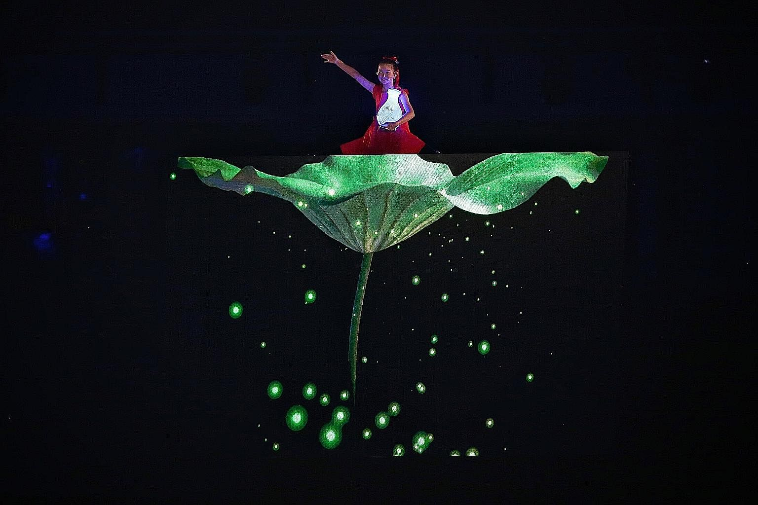 A young performer rises above the crowd with the announcement of Hangzhou as the host of the 2022 Asian Games during the closing ceremony of the 18th Asian Games in Jakarta. Thousands of athletes in ponchos marched in heavy rain at Gelora Bung Karno