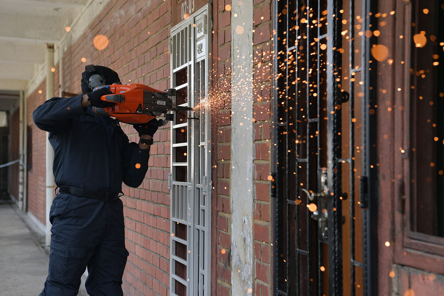 A Special Task Force officer demonstrating how to gain quick entry into a suspected trafficker's hideout using a motorised saw to cut open gates.