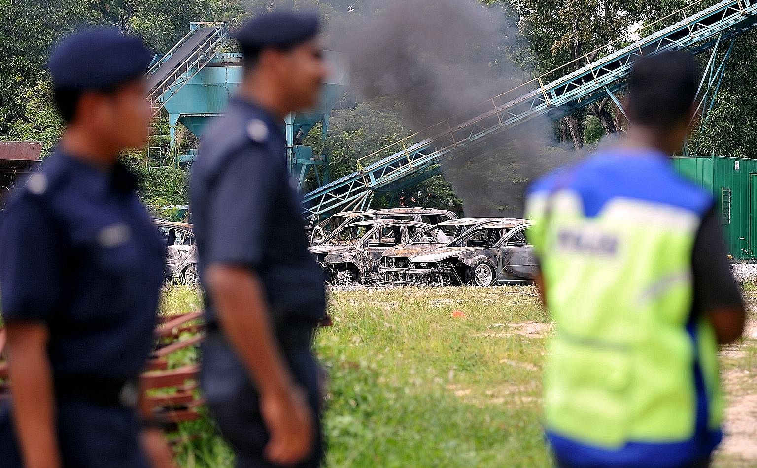 Policemen at the site of the Maha Mariamman Temple, where a riot broke out on Monday. In the background are some cars that were badly burnt in the incident. Prime Minister Mahathir Mohamad warns that those responsible will face stern action.