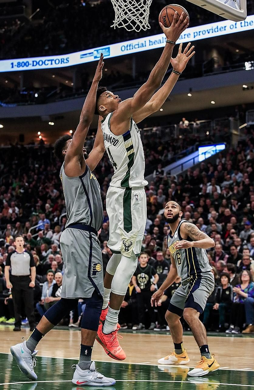 Milwaukee's Greek forward Giannis Antetokounmpo shooting between Indiana forward Thaddeus Young (left) and guard Cory Joseph during their NBA game at Fiserv Forum in Wisconsin. The Bucks, who are the first team to qualify for the play-offs, won 117-9