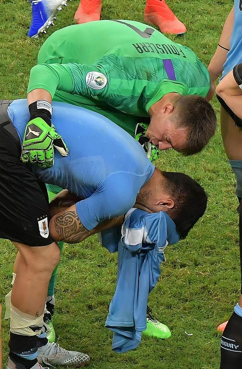 A distraught Suarez is comforted by Uruguay goalkeeper Fernando Muslera.