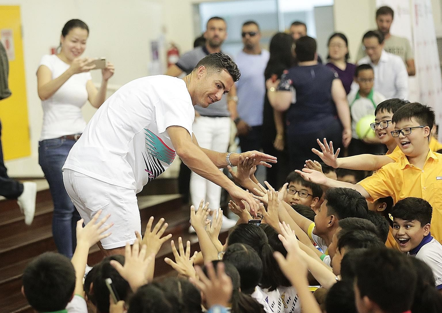 Portuguese football superstar Cristiano Ronaldo was at his charming best as he mingled with 1,000 upper primary pupils from Yumin and Chongzheng primary schools during a surprise visit to Yumin yesterday. Capturing the moment is Tampines GRC MP Cheng