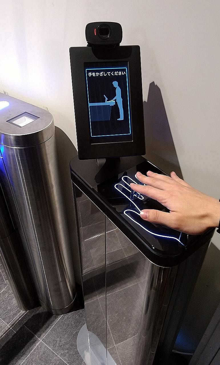 A customer trying out a palm reader installed at the entrance of a trial convenience store concept at Fujitsu's office in Kawasaki. This replaces checkout registers by using a non-contact, multi-biometric authentication system that enables identifica