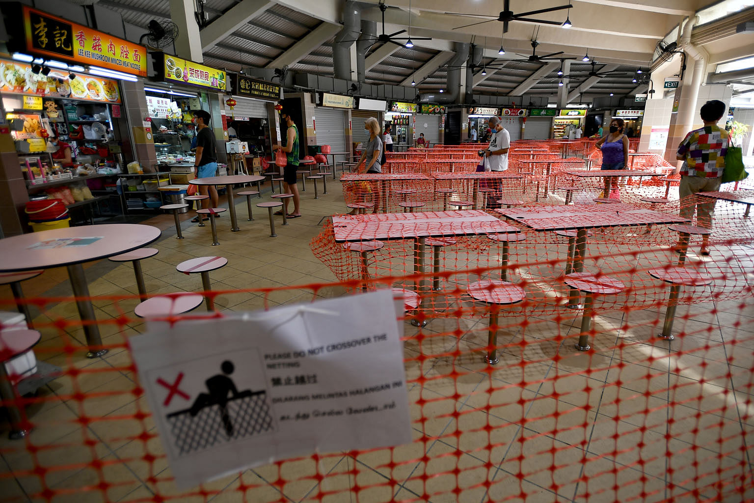 Patrons observing safe distancing while queueing for food at Tampines Round Market & Food Centre last Tuesday. This is part of the Government's precautionary measures for public health amid the coronavirus pandemic.