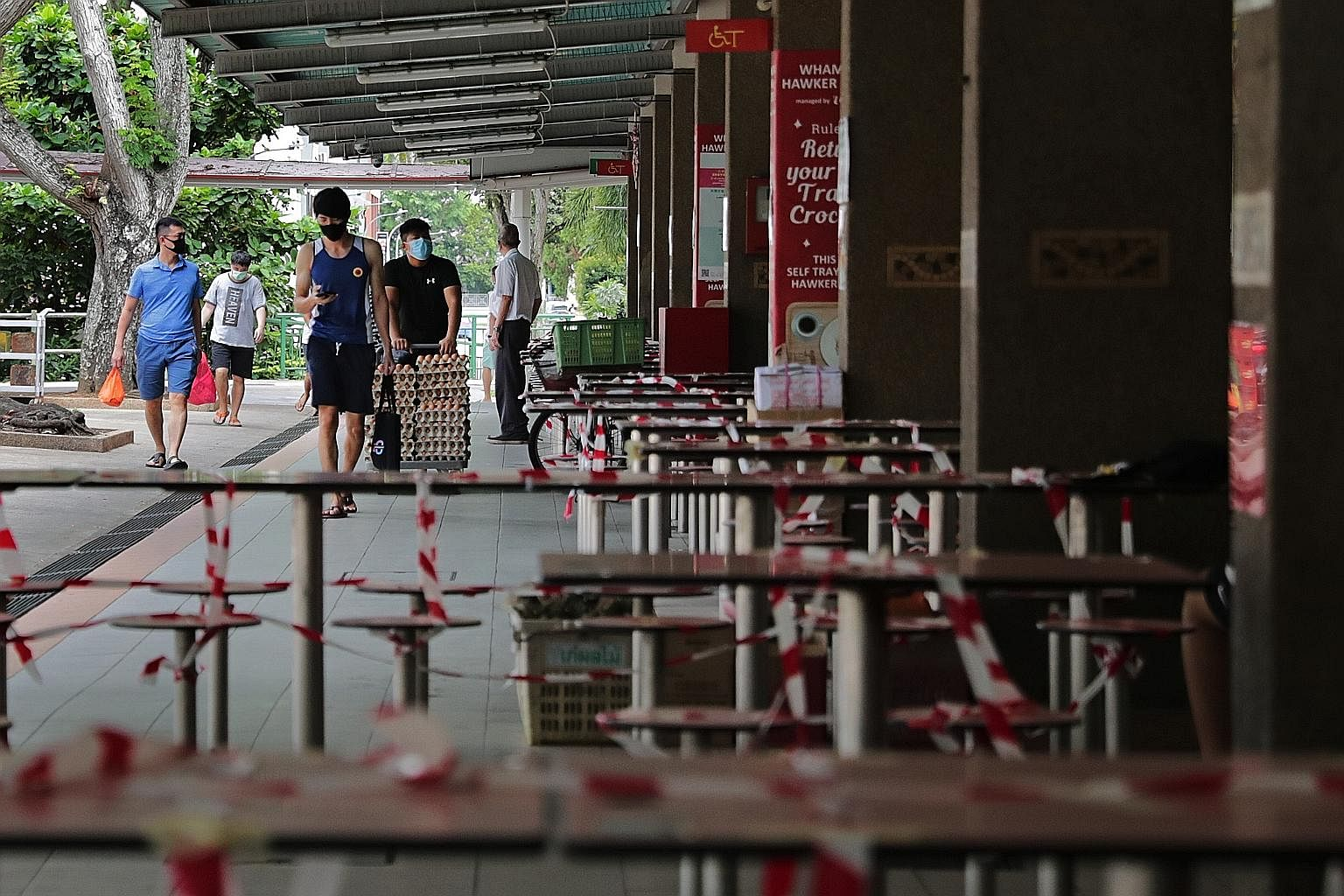 Taped-up tables and chairs at Whampoa Hawker Centre on Thursday, to stop people from dining in. In the first phase of reopening Singapore's economy, schools will gradually restart, and more Singaporeans will return to workplaces, though dining in wil