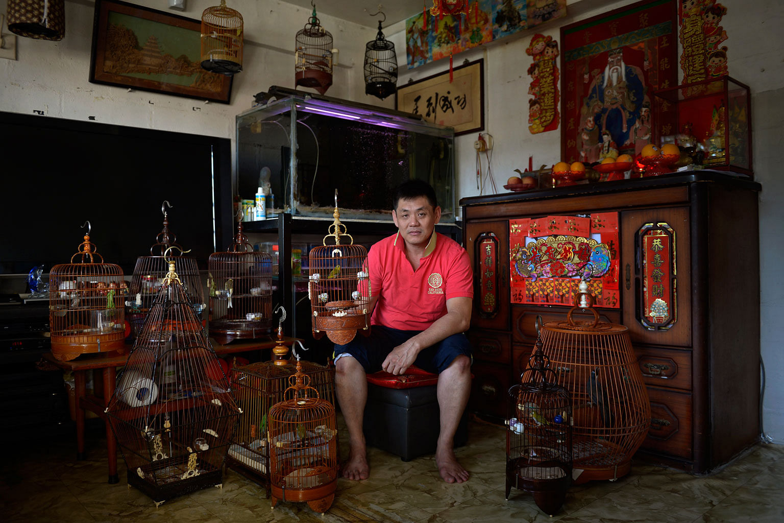 Mr Eric Ang, 46, with his pet birds in his living room. Mr Ang has lived in the estate all his life, and says that if he had the choice, he would not leave. He currently spends his time at home taking care of his bedridden elderly mother.
