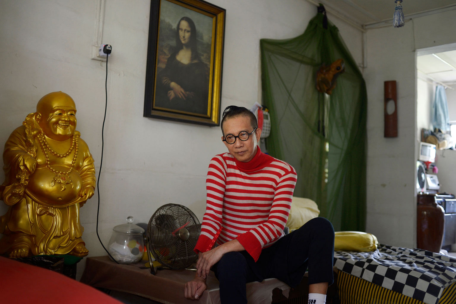 Mr Bilyy Koh, 61, in his living room. The decorations were inspired by his travels and work as a hairstylist in Europe and the Middle East. He has lived in the estate for more than 50 years and laments how the country is changing so quickly.